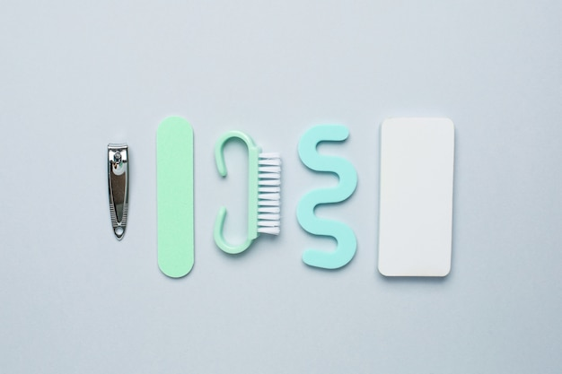 Pedicure manicure tools , nail file, pedicure scissors and separator for the fingers on blue background