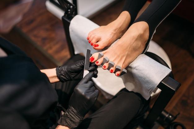 Мастер педикюра в черных перчатках полирует ногти пилкой, клиентка в салоне красоты.