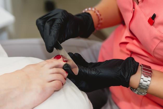 Мастер педикюра в черных резиновых перчатках выполняет процедуру ухода за ногтями. чистка ногтей пилкой. крупный план. педикюр в салоне красоты. гигиена и уход за ногами. понятие индустрии красоты