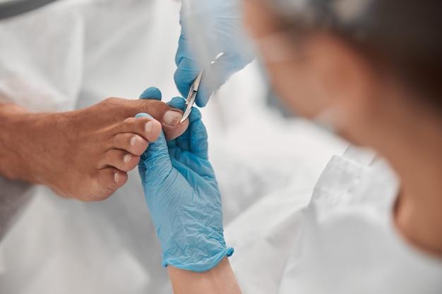 Мастер педикюра в перчатках подстригает ноготь клиента-мужчины в салоне красоты