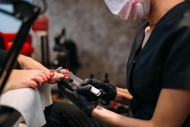 Мастер педикюра в перчатках полирует ногти пилкой
