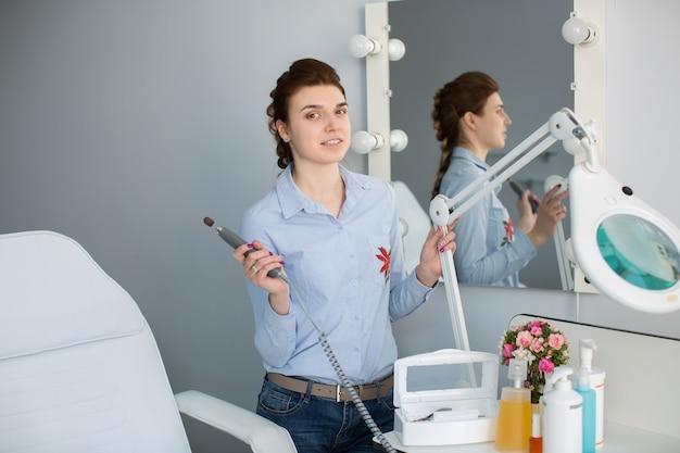 Мастер педикюра находится рядом с зеркалом в салоне и хранит устройство для педикюра