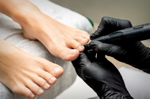 Pedicure master removes cuticle from toes of woman using professional electric nail hardware in nail salon