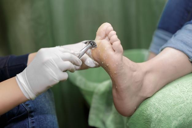 ビューティーサロンでのペディキュアの手順。足の角質を移動します。