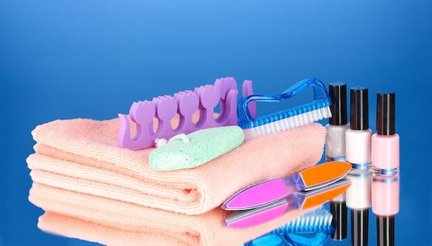 Pedicure set on pink towel on blue background