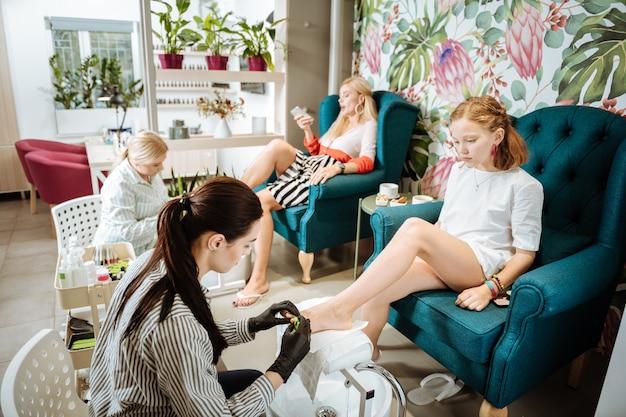 ペディキュア時間。ペディキュア中に快適な緑のアームチェアに座っているスタイリッシュなブロンドの髪の母と娘