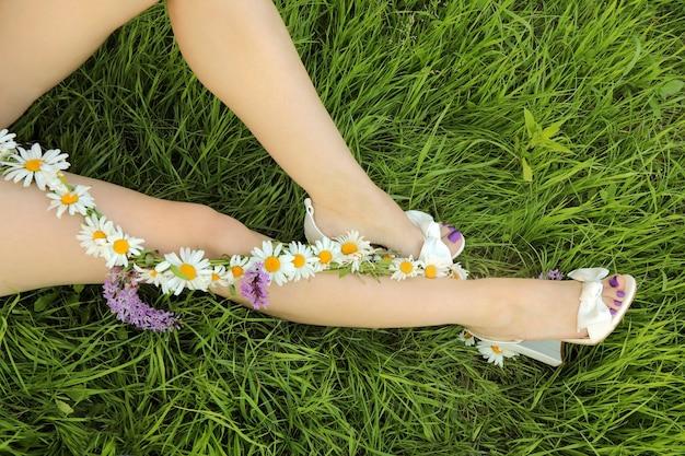 緑の芝生に座っている女の子にマットなライラックコーティングを施したペディキュア。足にデイジーのフラワーアレンジメントを施しています。