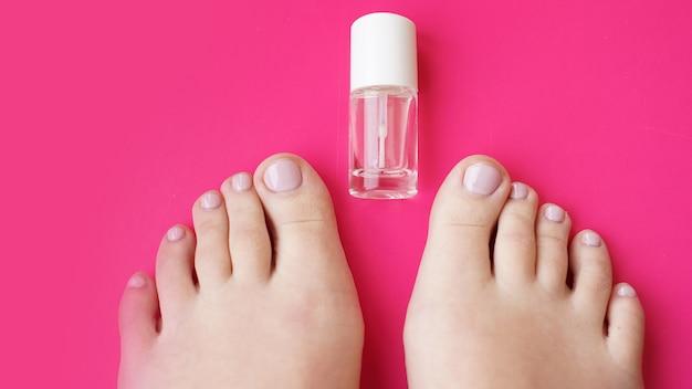 Педикюр с прозрачным лаком на розовом фоне. здоровые ноги, забота о здоровье