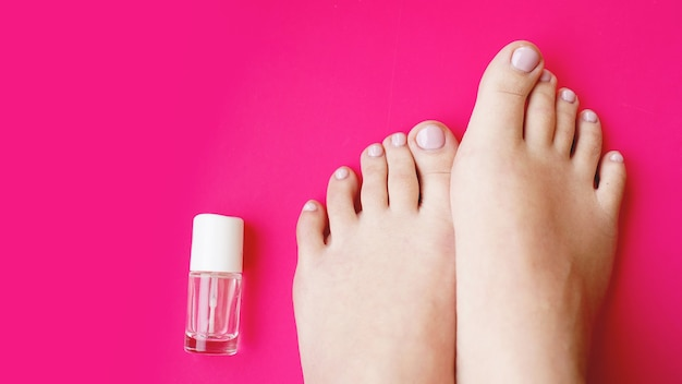 Pedicure with transparent nail polish on pink background. healthy feet, health care
