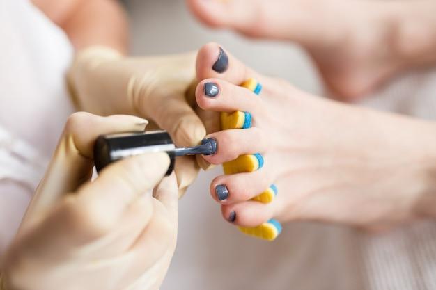 Педикюр наносит лак для ногтей