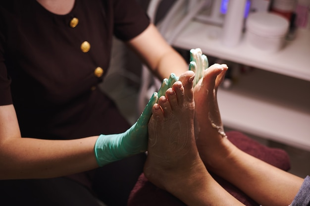 Pedicurist applying nourishing moisturizer cream on woman's legs and massaging them in pedicure room