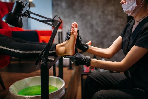 黒い手袋をはめた小児科医が美容院でクリーム色の女性クライアントをこすります。