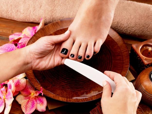 Pedicurist 마스터가 여성의 다리에 페디큐어를 만듭니다-스파 트리트먼트 개념