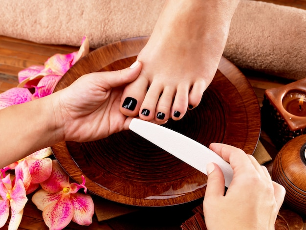 Il maestro del pedicurist fa la pedicure sulle gambe della donna - concetto di trattamento termale