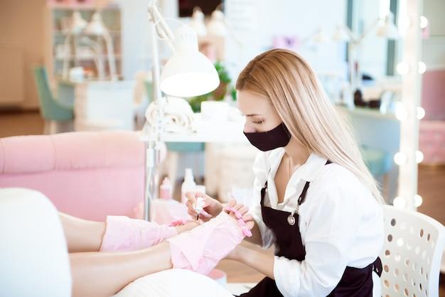 保護ゴム手袋をはめたペディキュリストの手で、足の爪にマニキュアを塗っています。