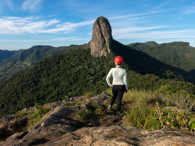山頂から岩山を探しているヘルメットをかぶっている女の子-pedra do bau