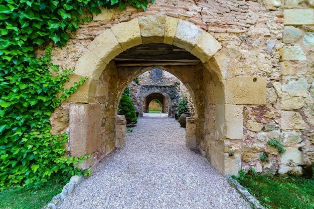 セゴビアのペドラザ城。石で作られた騎士の古い中世の宮殿。内部の石の道、緑の植物、アーチ、トンネルのある要塞。スペイン。