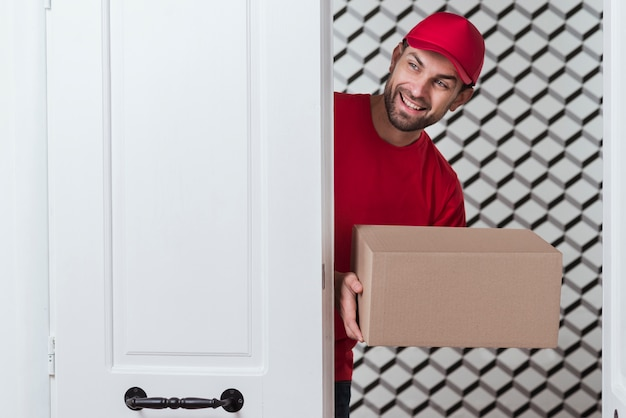 Peeking courier in red uniform holding box