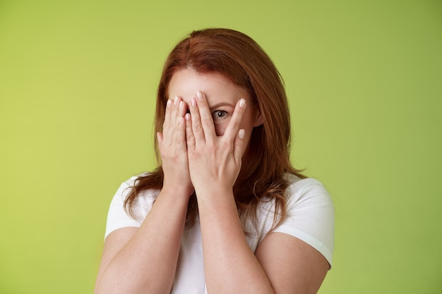 Not peeking playful charismatic middleaged ginger redhead woman close face palms look through fingers one eye stare camera intrigued waiting surprise gift stand green wall