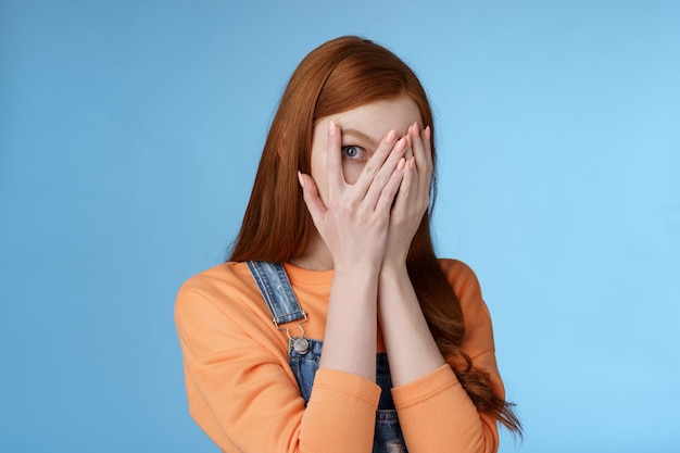Not peeking promise charming intrigued cute redhead teenage girl hiding face cover eyes palms look through fingers check out gift anticipating something interesting standing curious blue background
