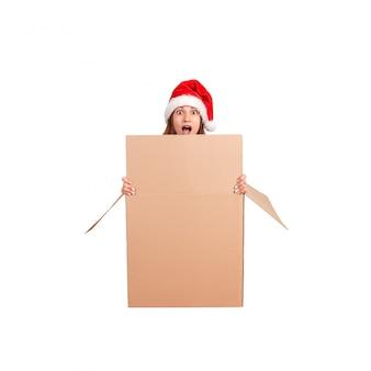 Сотрясенная женщина в шляпе рождества сидя из большой подарочной коробки и peeking над краем пустой пустой коробки. изолированный