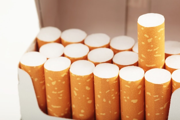 Peel it off cigarette pack prepare smoking on white wooden background. packing line up.  photo filters natural light.