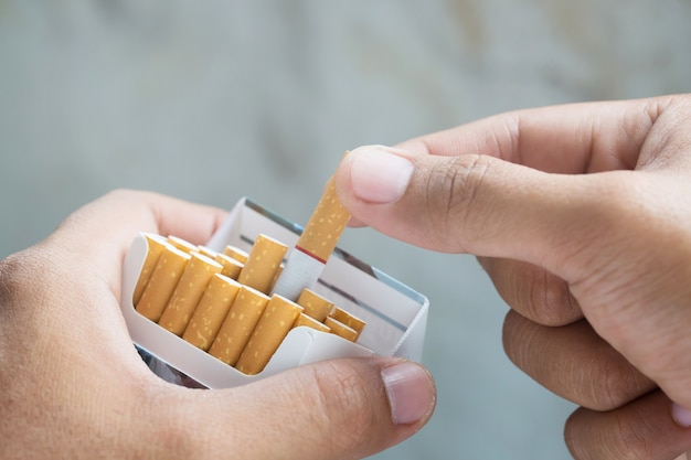 たばこを吸っているたばこパックからそれをはがします。写真フィルター自然光。