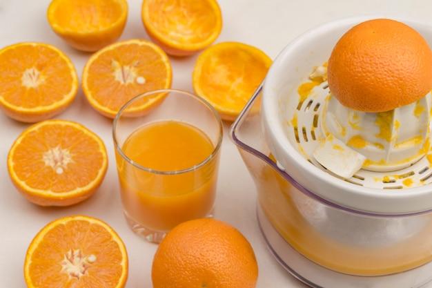 ジューサーで新鮮なオレンジの皮をむく。ジュースとオレンジのグラス