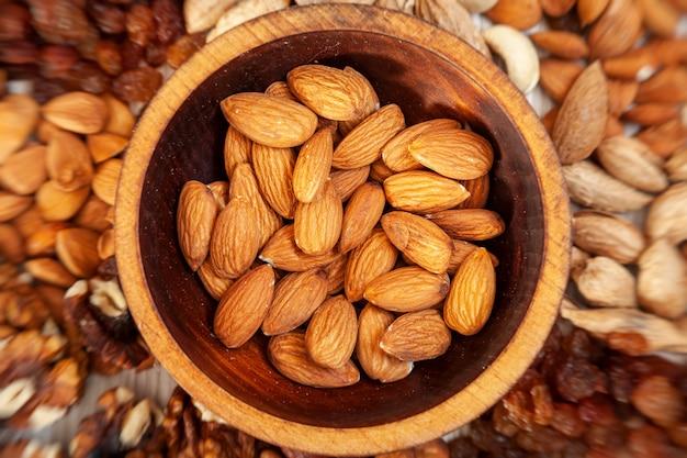 Очищенный миндаль в деревянной кедровой тарелке на фоне россыпи различных орехов.