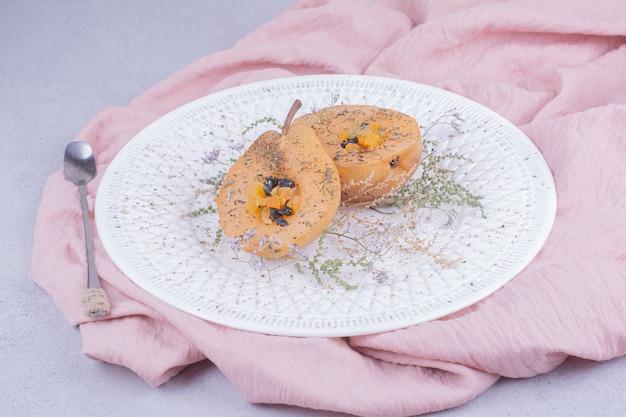 Очищенные и запеченные дольки груши с зеленью и специями в белой тарелке