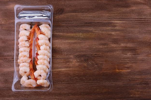 茶色の木製テーブルの上のプラスチック容器で皮をむいて調理したエビ