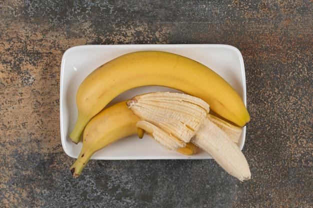 白いプレートに皮をむいたバナナと皮をむいていないバナナ
