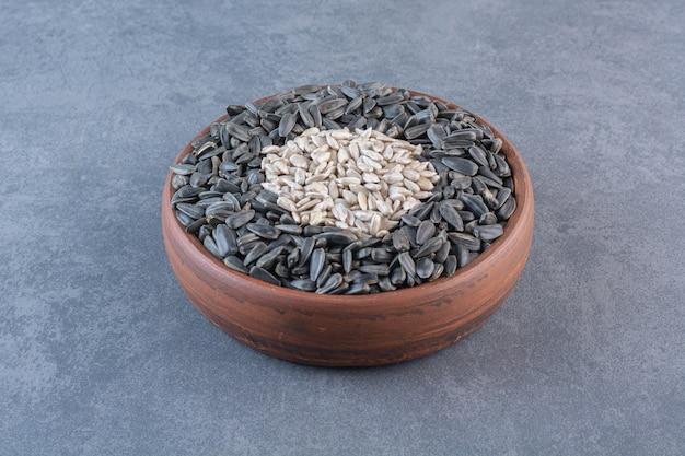 大理石の表面に、木製のボウルに皮をむいた、皮をむいていないヒマワリの種