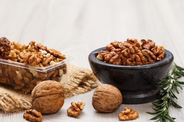 껍질을 벗긴 호두와 껍질을 벗기지 않은 호두는 나무 배경에 자루천과 로즈마리가 있는 플라스틱 용기와 돌 그릇에 있습니다. 유용한 영양가 있는 단백질 제품.