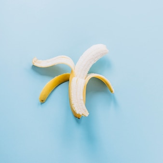 Peeled banana on blue background