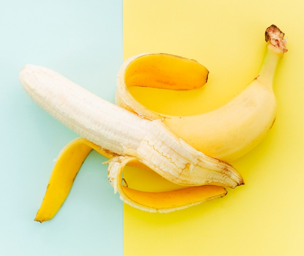 Peeled banana on colored background