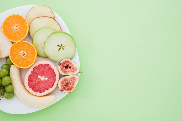Peeled banana; grapes; orange; grapefruit; fig and slices of apple and pear fruit on white plate over the mint green backdrop