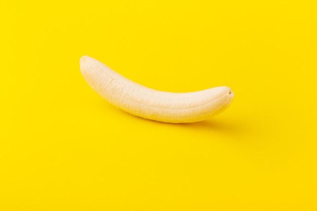 Очищенный банан на желтом фоне, концепция минимальной диеты