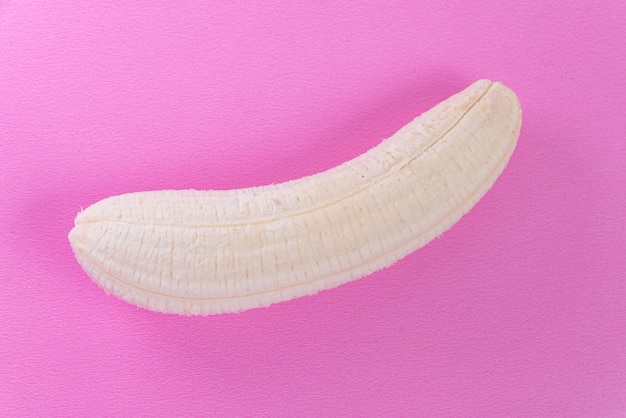 Peeled banana on the pink surface