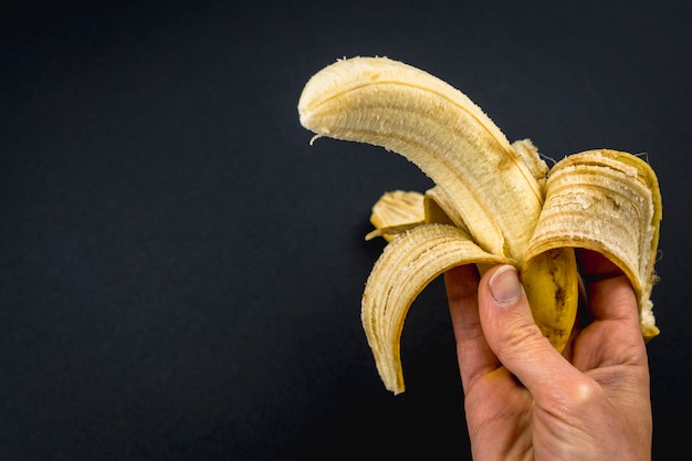 A peeled banana in a woman's hand on black