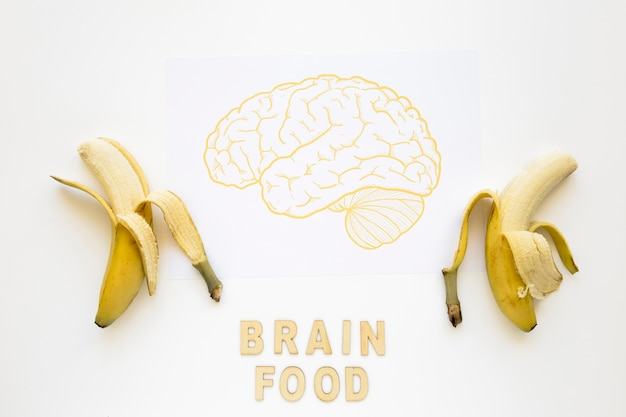 Peeled bananas near brain food words with drawing on paper