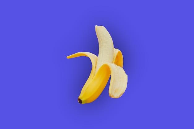 素敵な青い背景と影のおいしい黄色の熟したバナナの皮をむいたバナナ