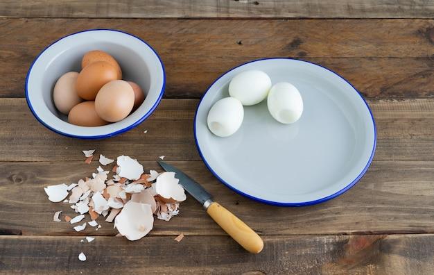 Очищенные вареные яйца на белой тарелке. деревянная поверхность. скопируйте пространство. яичная скорлупа.
