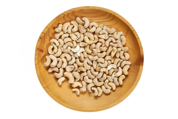 Peeled cashew  in a wooden pine plate on a white isolated. row of bowls with cashew   nuts, top view.