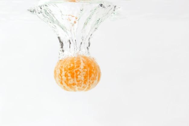 水に落ちる皮をむいた柑橘類のオレンジ