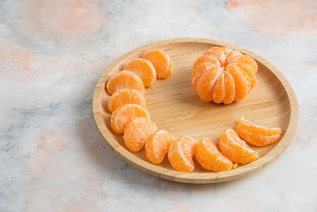 Peeled clementine mandarins over wooden plate