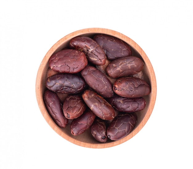Peeled cocoa beans in the wooden bowl, isolated. roasted and aromatic cocoa beans, natural chocolate. top view. macro.