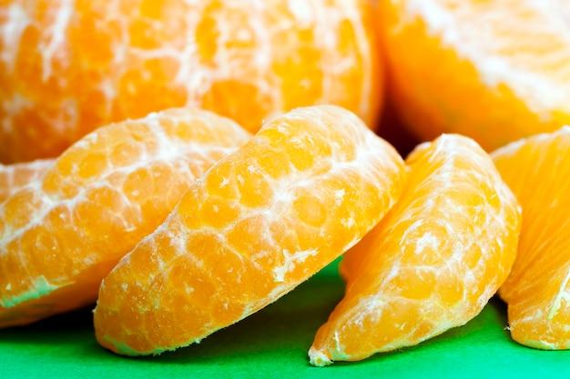 皮をむいたおいしいオレンジの準備ができて、緑の上に横たわっている部分
