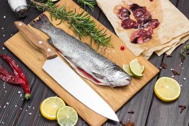 도마에 껍질을 벗긴 생선 송어와 칼. 종이에 생선 찌꺼기. 로즈마리와 백리향 테이블에 레몬 웨지. 어두운 나무 배경입니다. 플랫 레이