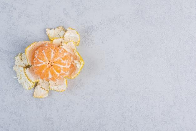 Mandarino fresco sbucciato su sfondo grigio.